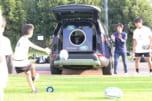 ランドローバーの広々としたトランクにラグビーボールを蹴り入れる